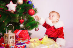 Baby in Santa costume at the Christmas tree Royalty Free Stock Photo