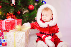 Baby in Santa costume at the Christmas tree Stock Photo