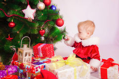 Baby in Santa costume at the Christmas tree Stock Photos