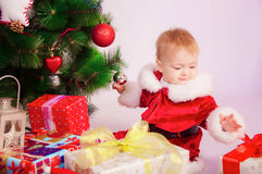 Baby in Santa costume at the Christmas tree Stock Image