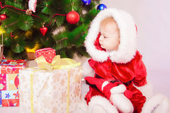 Baby in Santa costume at the Christmas tree Stock Images