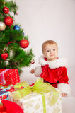 Baby in Santa costume at the Christmas tree Royalty Free Stock Images