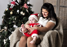 Baby in Santa costume with mother sit on chair near Christmas tree Stock Photo