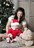 Baby in Santa costume sit with mother on decorating Christmas tree Stock Images