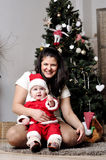 Baby in Santa costume sit with mother on decorating Christmas tree Royalty Free Stock Photos