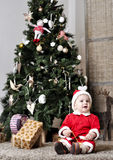 Baby in Santa costume sit near decorating Christmas tree. Child in Santa costume sit near decorating Christmas tree and look Stock Image