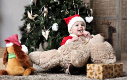 Baby in Santa costume sit near decorating Christma. S tree with two toys Royalty Free Stock Photos