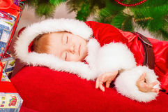 Baby in Santa costume sleeping at the Christmas tree Royalty Free Stock Image