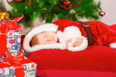 Baby in Santa costume sleeping at the Christmas tree Stock Photos
