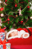 Baby in Santa costume sleeping at the Christmas tree Stock Photography