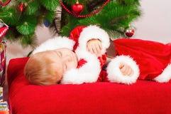 Baby in Santa costume sleeping at the Christmas tree Royalty Free Stock Photos