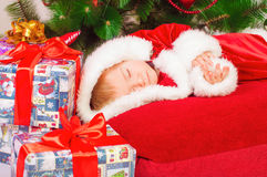 Baby in Santa costume sleeping at the Christmas tree Stock Image