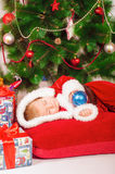 Baby in Santa costume sleeping at the Christmas tree Royalty Free Stock Photography