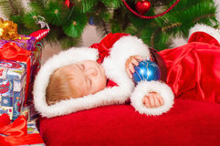 Baby in Santa costume sleeping at the Christmas tree Royalty Free Stock Photo