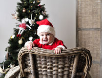 Baby in Santa costume stand on chair near Christmas tree Stock Photo