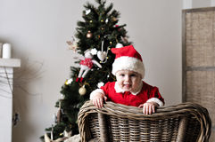 Baby in Santa costume stand on chair near Christmas tree Stock Image