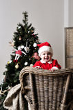 Baby in Santa costume stand on chair near Christmas tree Royalty Free Stock Photography
