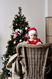 Baby in Santa costume stand on chair near Christmas tree Royalty Free Stock Photos