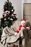Baby in Santa costume stand on chair near Christmas tree Royalty Free Stock Image