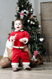 Baby in Santa costume standing with mother on decorating Christmas tree Royalty Free Stock Photography