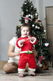 Baby in Santa costume standing with mother on decorating Christmas tree Royalty Free Stock Image