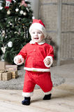 Baby in Santa costume walking near decorating Christmas tree Royalty Free Stock Images