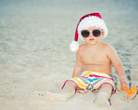 Baby Santa. Cute baby wearing Santa hat on the beach Stock Photo