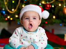 Baby in a Santa Hat. Serious Baby in a Christmas hat royalty free stock photography