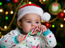Baby in a Santa Hat. Serious Baby in a Christmas hat with a Candy Cane stock photos