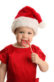 Baby in Santa hat with Candy Cane. Christmas Portrait of a beautiful little child girl wearing a santa hat and holding a candy cane Stock Photos