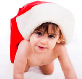 Baby in santa hat crawling Stock Image