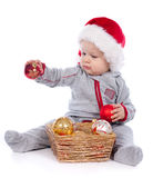 Baby in Santa hat playing with Christmas balls Royalty Free Stock Photos