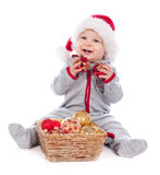 Baby in Santa hat playing with Christmas balls Royalty Free Stock Photography