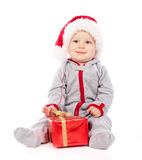 Baby in Santa hat playing with Christmas gift box Stock Image