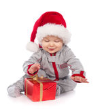 Baby in Santa hat playing with Christmas gift box Stock Photos