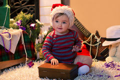 Baby in Santa hat sits on the carpet and openning a box Royalty Free Stock Images