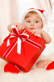 Baby santa holds a big red gift box. Cute baby santa holds a big red gift box Royalty Free Stock Images