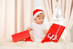Baby santa holds a big red gift box. Baby santa holds a big red present box Royalty Free Stock Photo
