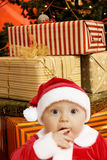 Baby santa with presents. Baby in Santa uniform in utter surprise, a lot of present boxes behind Stock Image