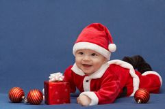 Baby in santa's suit. With gift and christmas balls stock photos