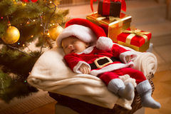Baby Santa sleeping under Christmas tree with presents Stock Photo