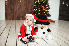 Baby in santa suit on the floor near xmas tree Stock Photo