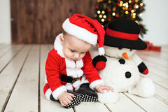 Baby in santa suit on the floor near xmas tree Stock Photography