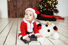 Baby in santa suit on the floor near xmas tree Stock Images