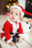 Baby in santa suit on the floor near xmas tree Royalty Free Stock Photos