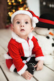 Baby in santa suit on the floor near xmas tree Stock Image