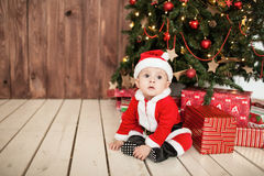 Baby in santa suit with gifts near xmas tree Stock Photography