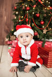 Baby in santa suit with gifts near xmas tree Royalty Free Stock Photography
