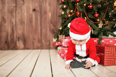 Baby in santa suit with gifts near xmas tree Stock Photo
