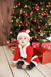 Baby in santa suit with gifts near xmas tree Stock Image